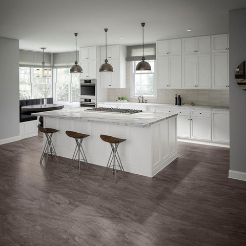 Large, modern kitchen with charcoal tile floors and a light grey tile backsplash above the counters with white cabinets