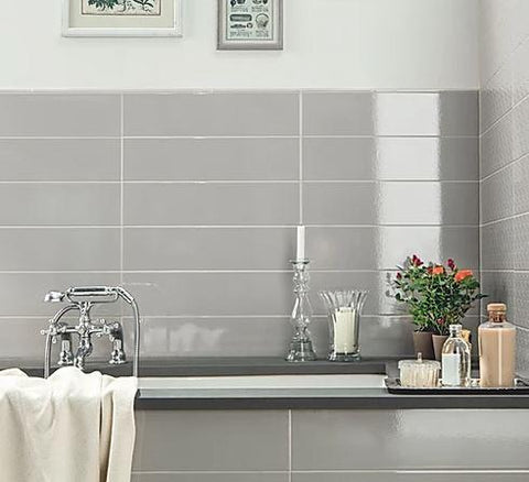 Grey long glossy crackle tile around a tub surround with trim.