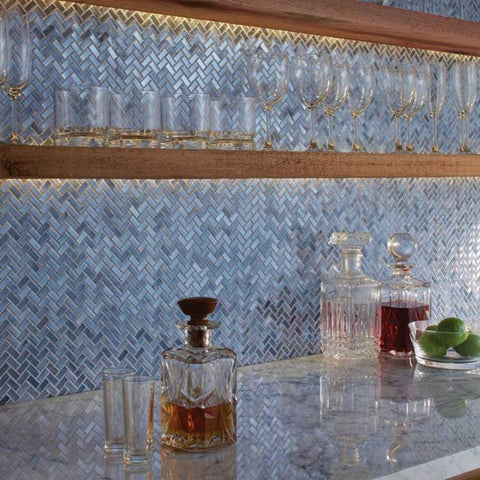 Intricate blue mosaic tile bar backsplash with various glassware on countertop