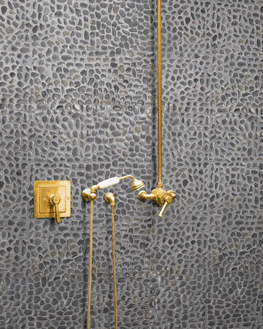 Black Pearl Round pebbles in shower with brass fittings