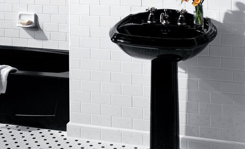 Black and white hexagon bathroom floor tiles with black sink, black bathtub and white, rectangular tile walls