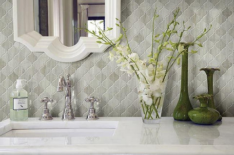 Bathroom with gray, polished tile wall, clean white countertops, and flower vases