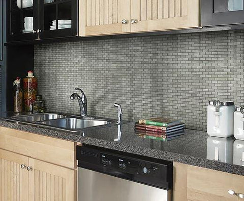 Dark kitchen countertops and birch cabinets against limestone tile wall in mini brick mosaic
