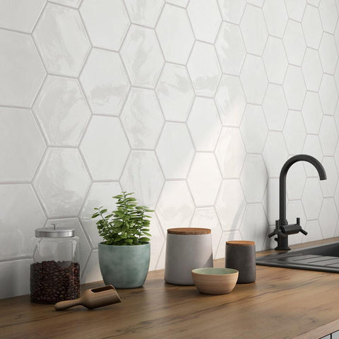 "Closeup of White 7"" hexagon tiles on the backsplash of a modern kitchen with butcherblock counters."