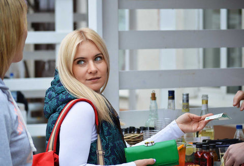 Woman making purchase looking over shoulder at friend as if asking a question