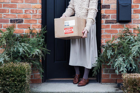 Woman picking up delivered package from doorstep