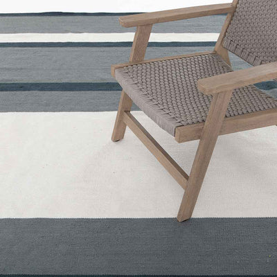 Senna Navy & Cream Outdoor Rug stripes Four Hands  lifestyle light brown chair