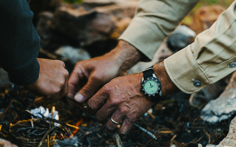 Two people start a camp fire, highlights bright green dial of watch worn