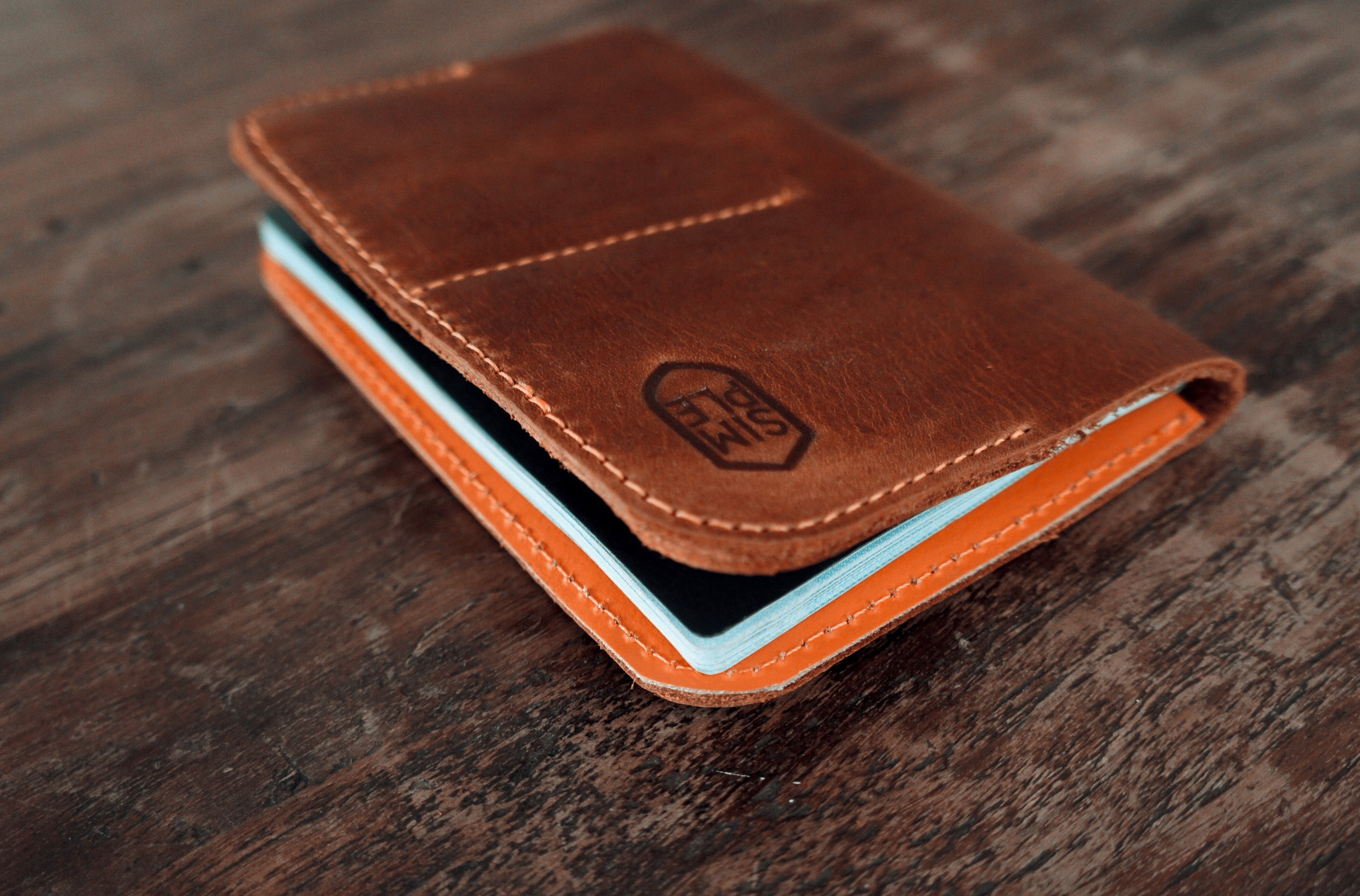 Handmade brown leather passport wallet, with orange inside