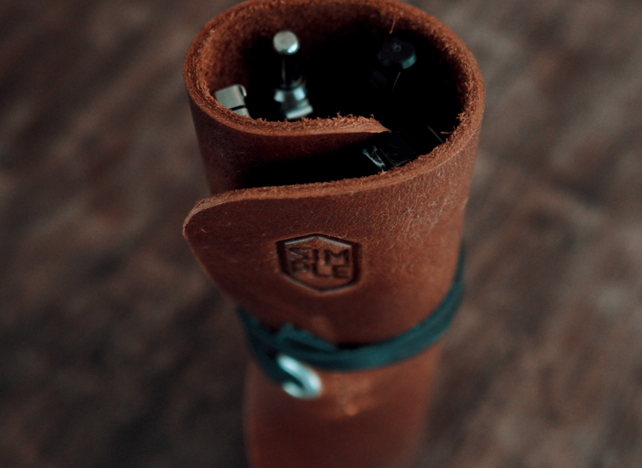 Brown leather pen wrap, rolled up with black strap
