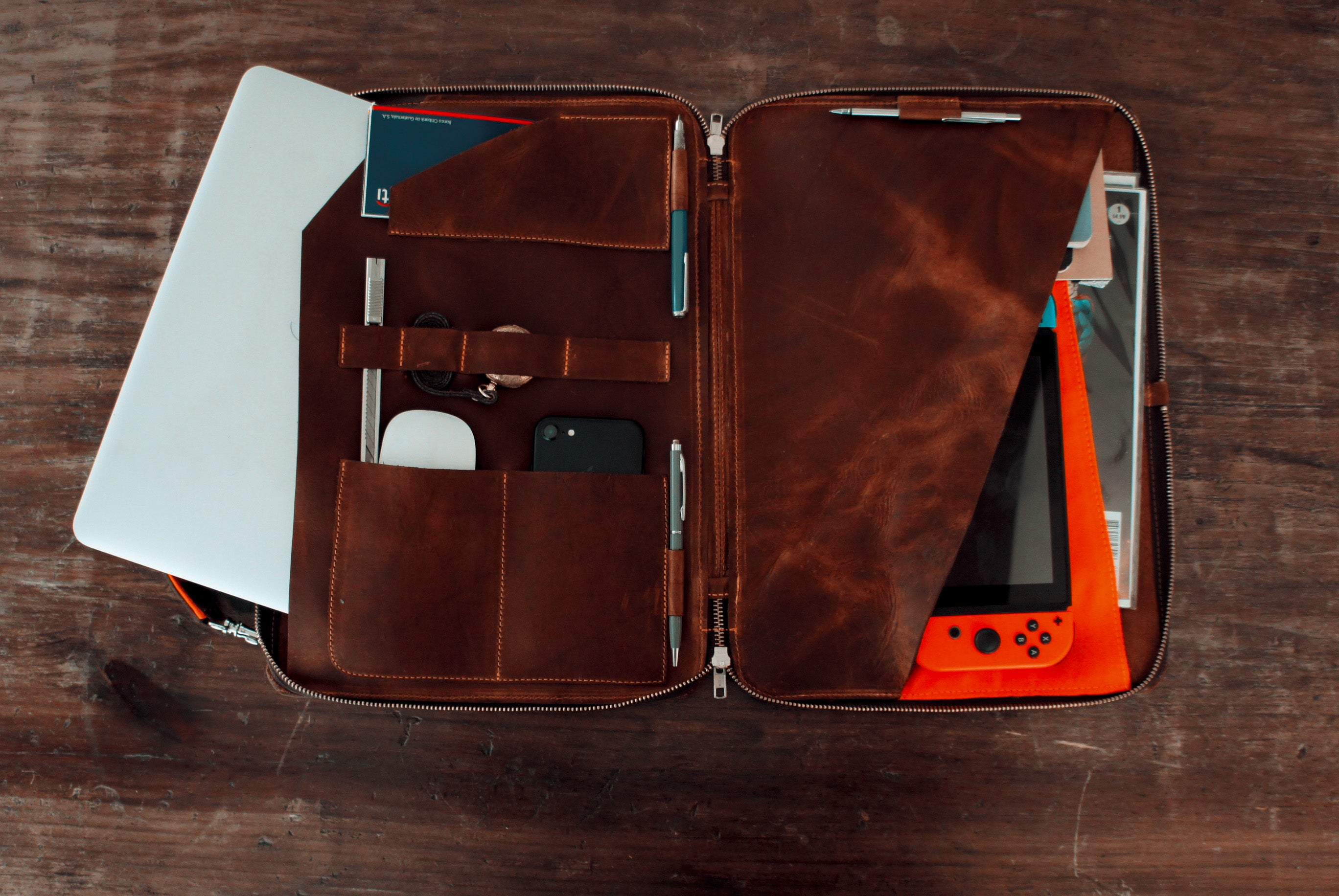 brown leather portfolio, shoulder and hand strap, with orange accents, inside full