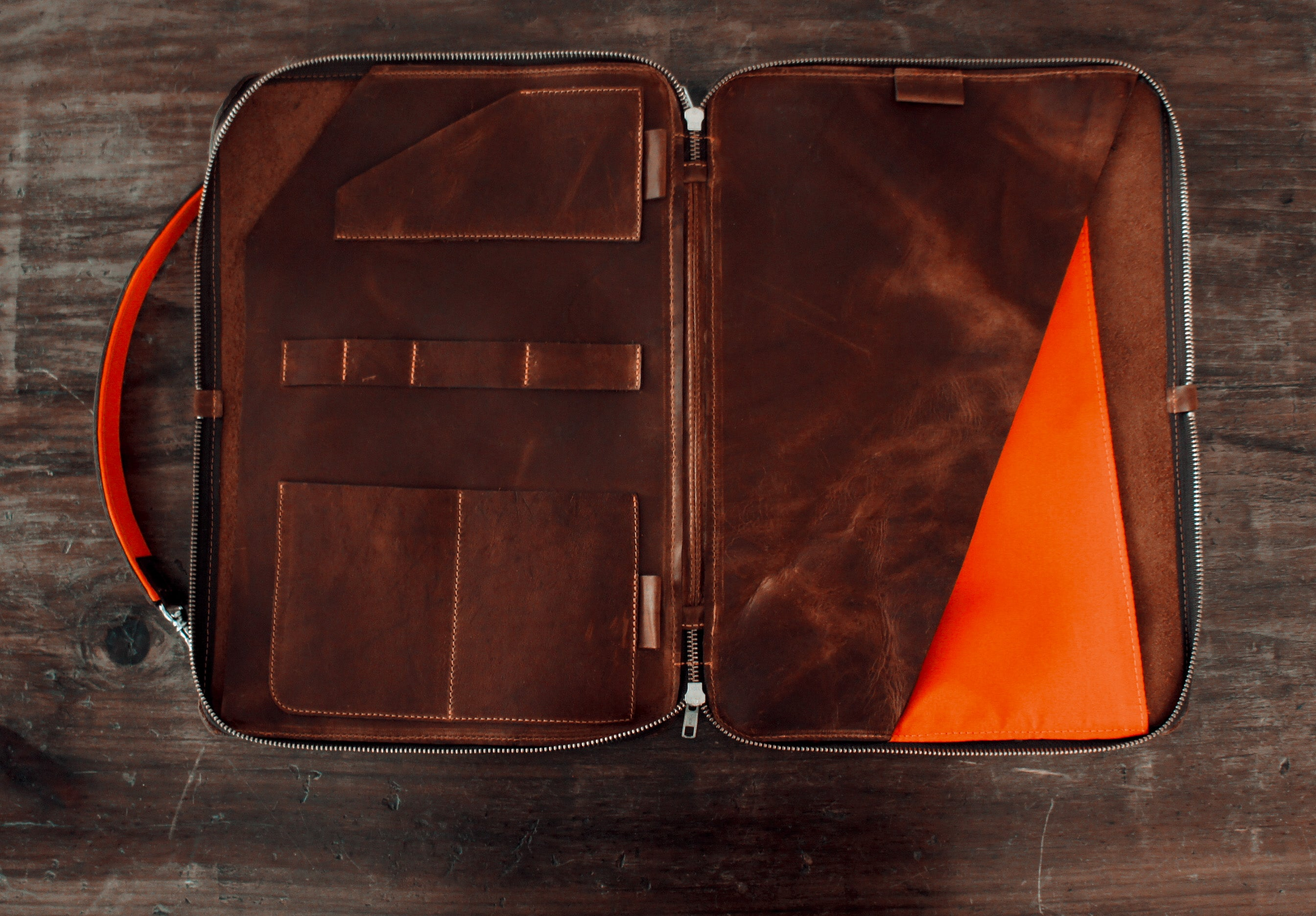 brown leather portfolio, shoulder and hand strap, with orange accents, inside