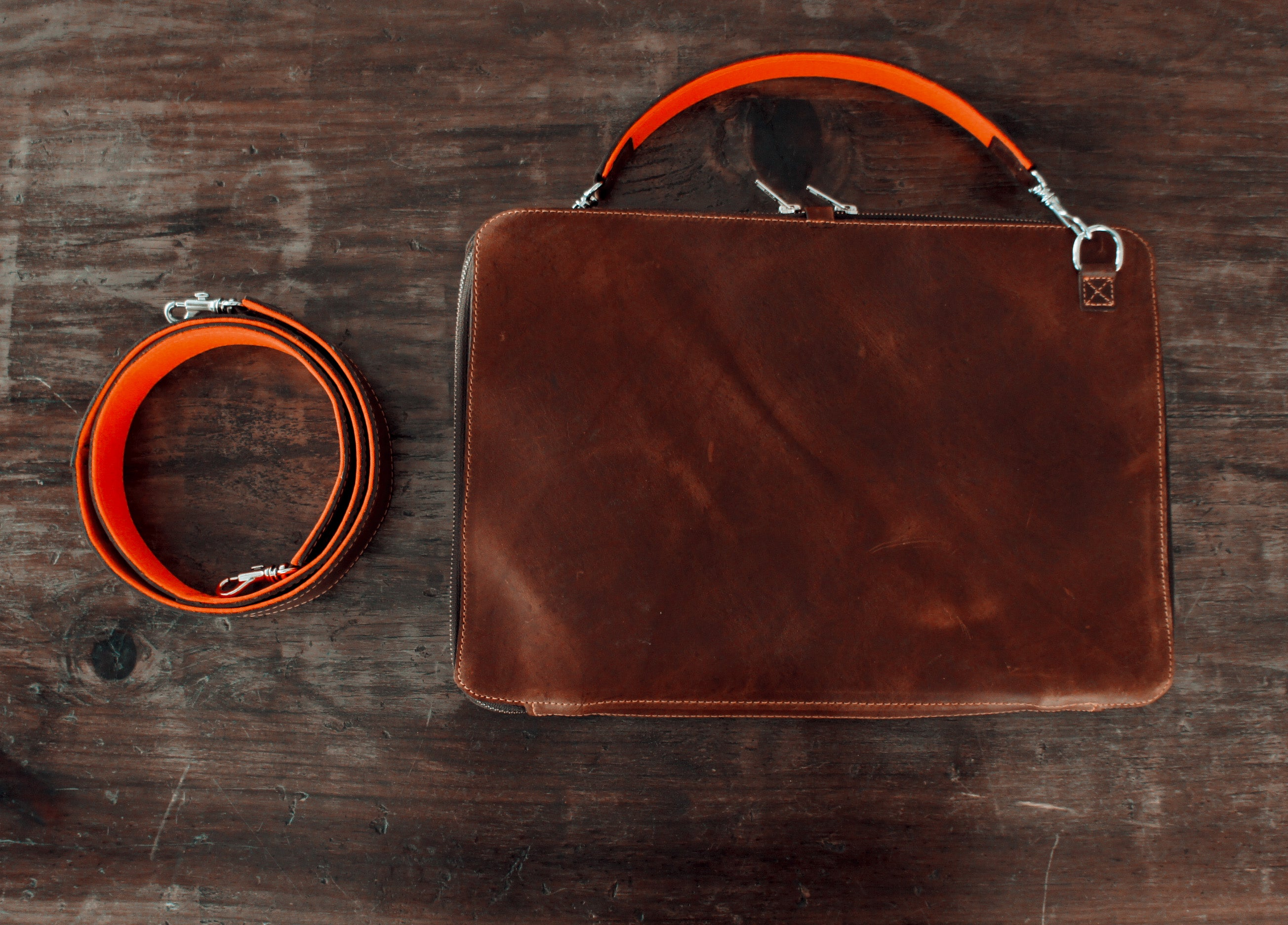 brown leather portfolio, shoulder and hand strap, with orange accents, back side