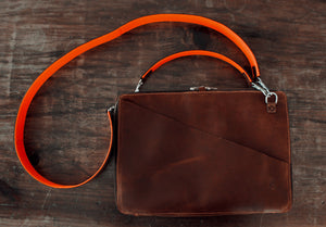 brown leather portfolio, shoulder and hand strap, with orange accents, front side