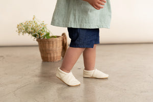 cream leather slip on baby shoes in a gender neutral style. Shown on girl