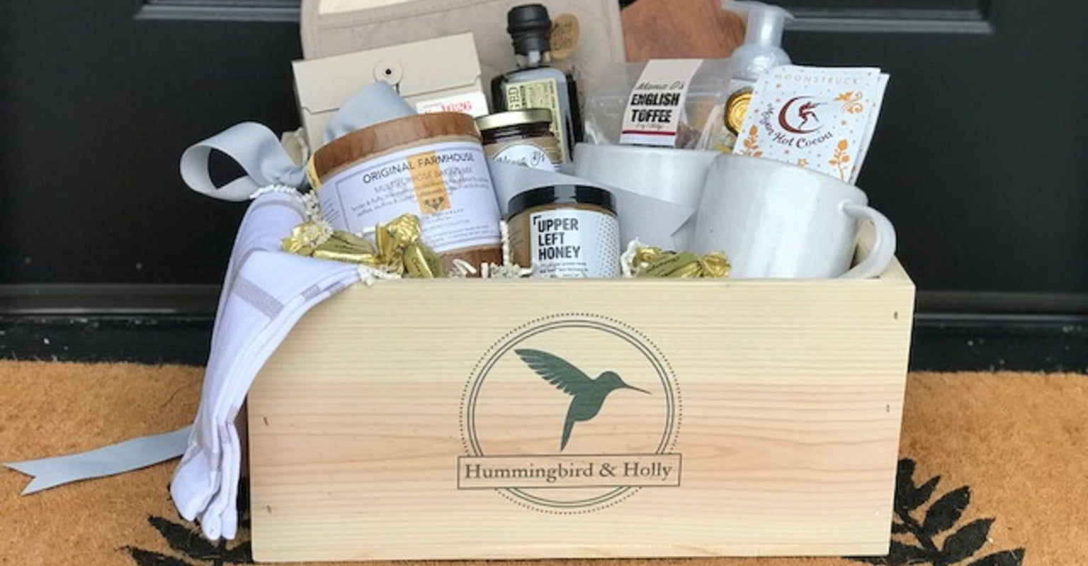 Custom Crate with Belle Epicurean baking mix, woodinville whiskey syrup, Smith Teamaker tea, dish towel, 2 coffee mugs, Moonstruck cocoa,, a beuatiful cutting board and Michel Designs hand soap - the perfect gift to welcome someone to a new home.