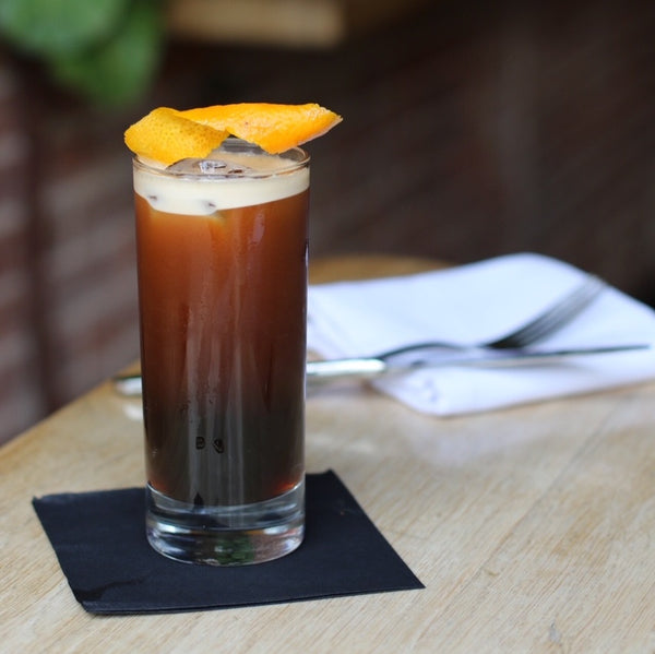 Iced RISE nitro cold brew coffee cocktail served in a glass with a garnish at a restaurant