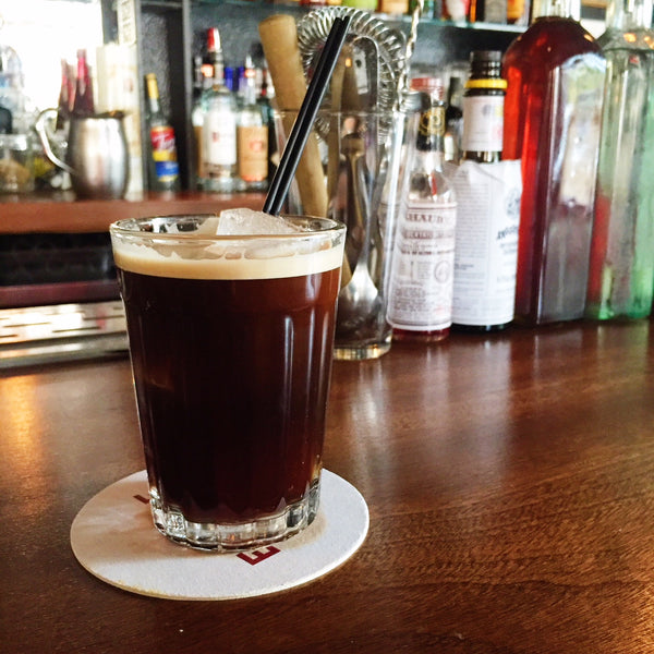 RISE nitro cold brew cocktail served in glass with straw at a bar