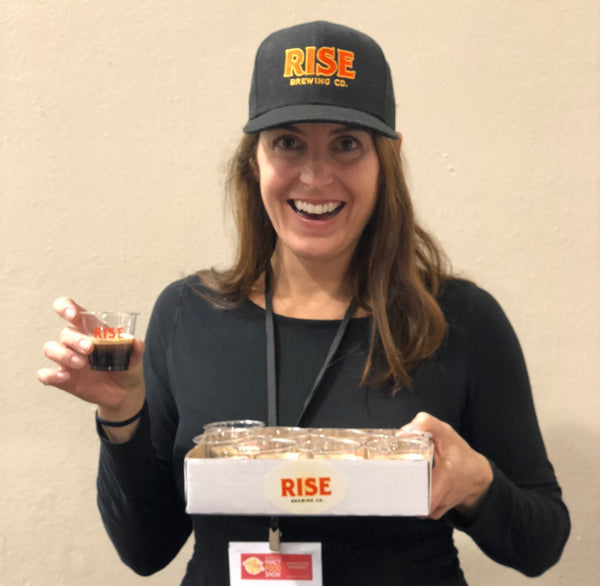 Lindsay Potter with RISE Brewing Co. Original Black nitro cold brew coffee and merchandise