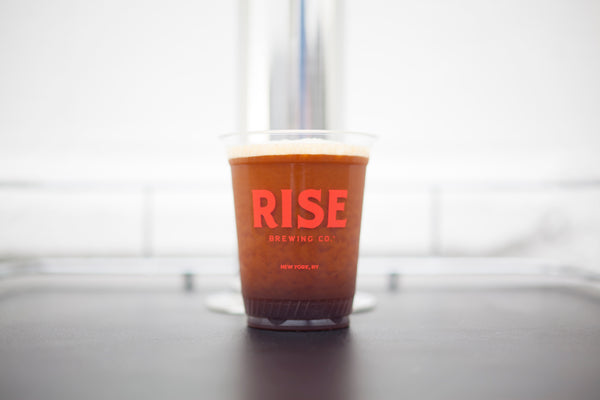 Organic, non-GMO RISE nitro cold brew coffee poured in a cup with creamy, frothy head