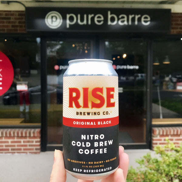 Organic, non-GMO RISE nitro cold brew coffee in a can in front of Pure Barre, fueling athletes and workouts