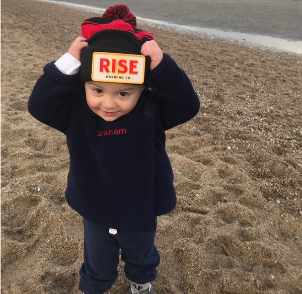 Baby with RISE Nitro Cold Brew Coffee hat on the beach