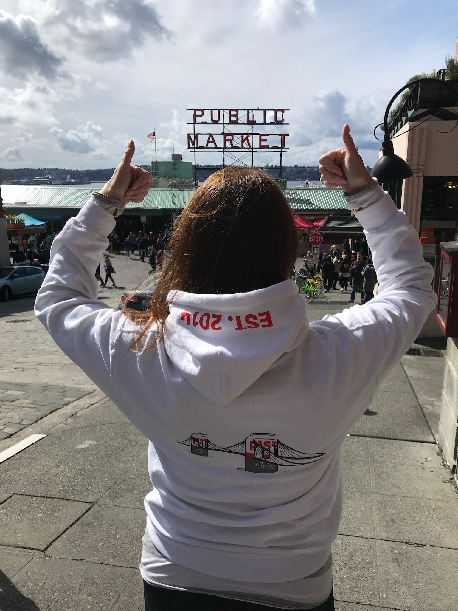 Woman wearing RISE hoodie sweater with cans in Seattle Pike Place Public Market - RISE Brewing Co.