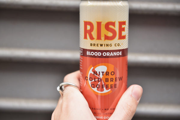 Organic, non-GMO RISE Coffee - Blood Orange Nitro Cold Brew - with customer holding can