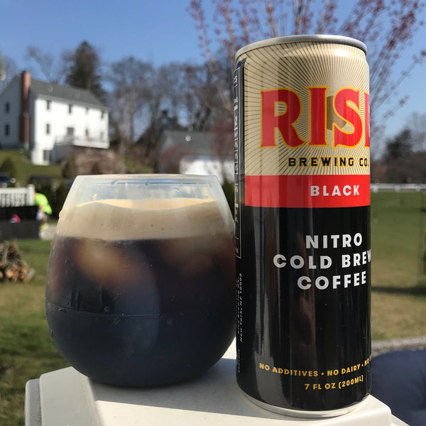 RISE nitro cold brew coffee -- organic, non-GMO, sustainably-sourced beverage in a can and in a glass -- on a farm