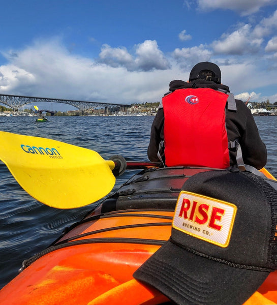 RISE Brewing Co. (maker of RISE coffee) branded baseball cap in boat in Seattle, Washington (Pacific Northwest)