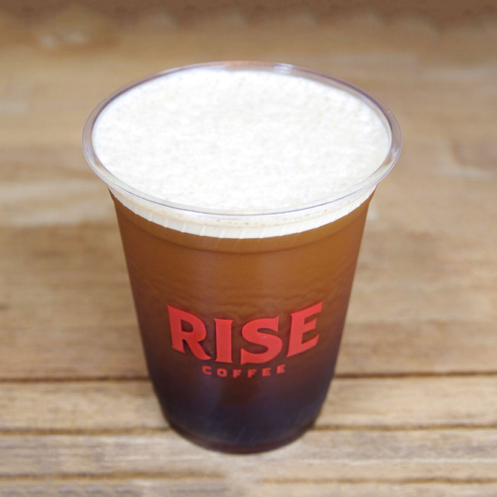 Cup of creamy, frothy, non-GMO, non-dairy, and organic RISE nitro cold brew coffee with cascade - RISE Brewing Co.