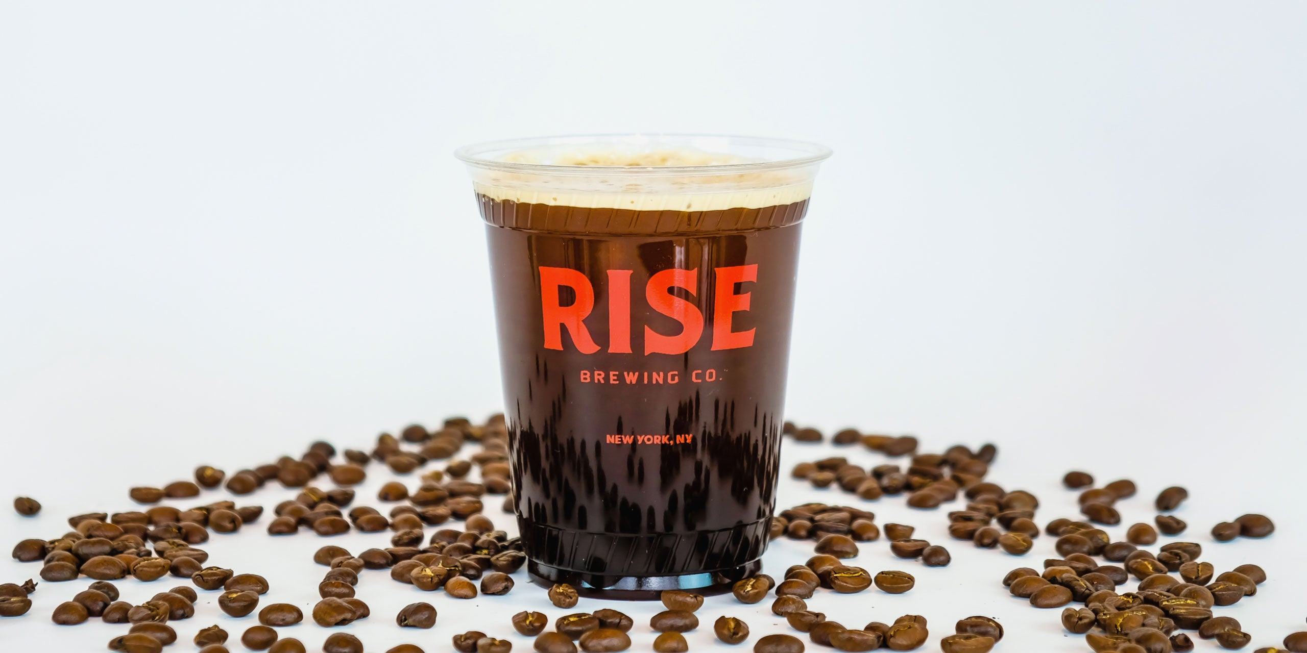 RISE nitro cold brew coffee in Original Black flavor with coffee beans - RISE Brewing Co.