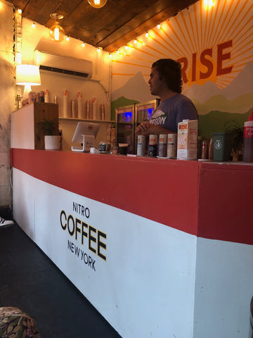 RISE Nitro Brewing Co Cafe Twinkle Lights - barista in coffee shop serving customers