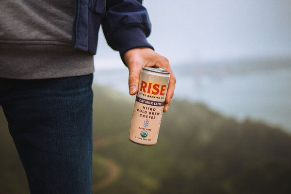 RISE Oat Milk Latte |  Man holding coffee can in hand while adventuring | RISE Nitro Brewing Co.