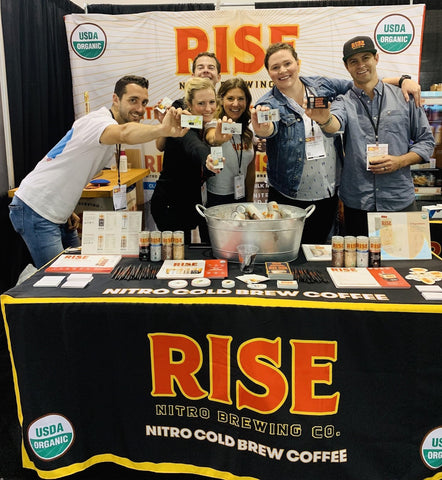 RISE Nitro Brewing Co. team sampling nitro cold brew coffee in all 4 flavors: original black, oat milk latte, oat milk mocha, and classic latte