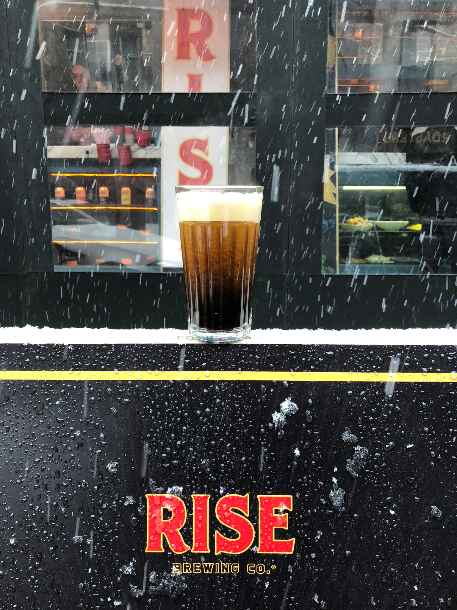 Glass of RISE nitro cold brew coffee in the snow, outside of cafe - RISE Brewing Co.