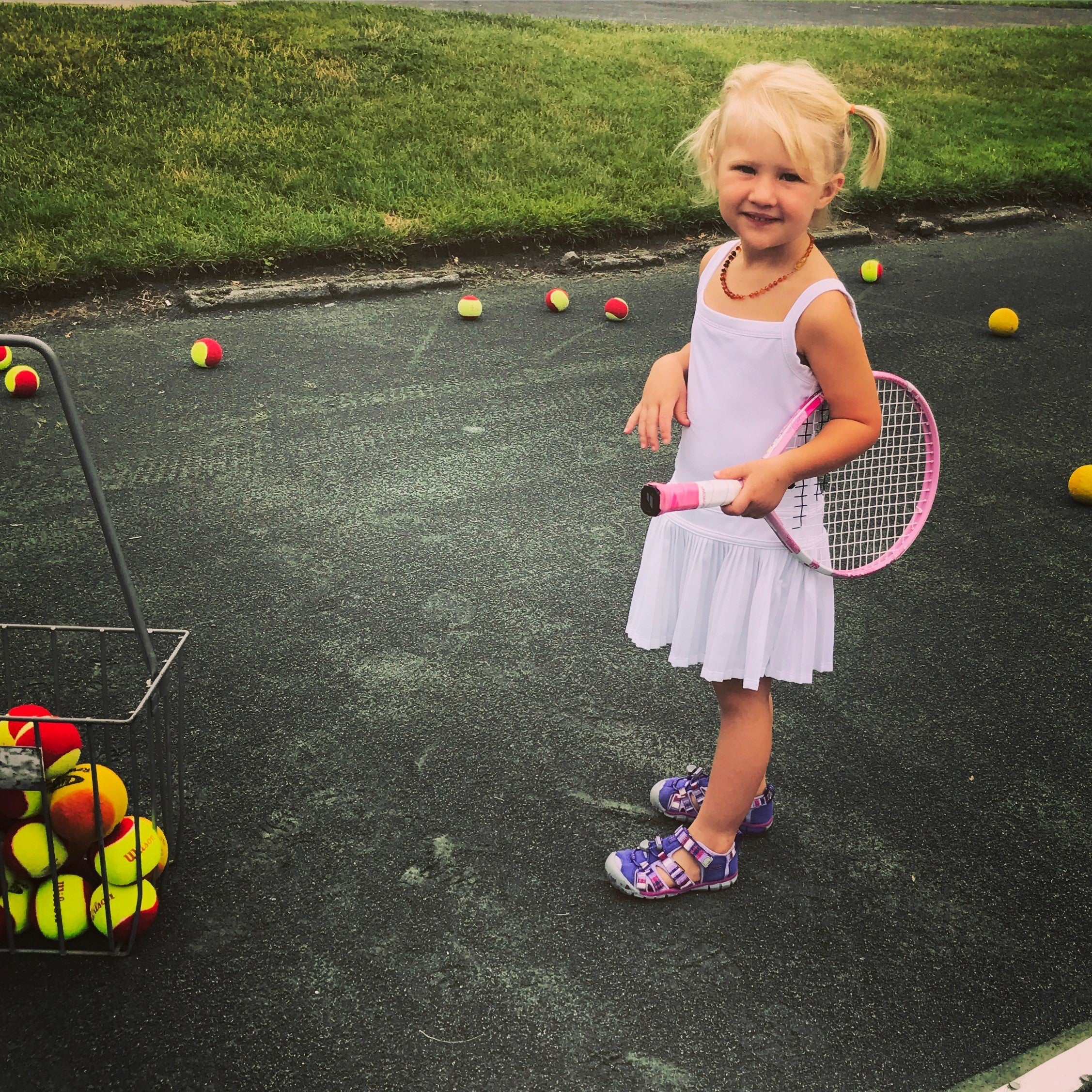 Mia with Tennis Racket and Tennis Balls | RISE Nitro Brewing Co.