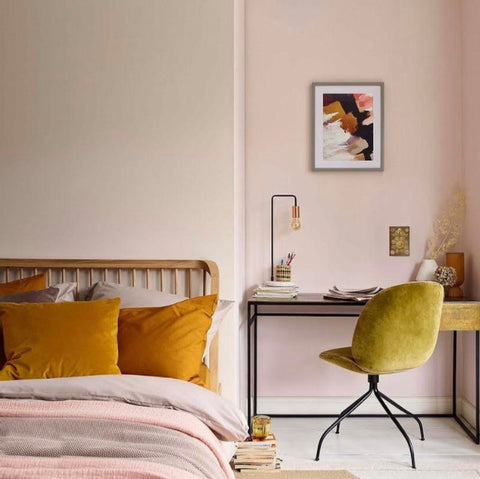 abstract painting featuring pinks, oranges, and yellows in a warm-toned bedroom