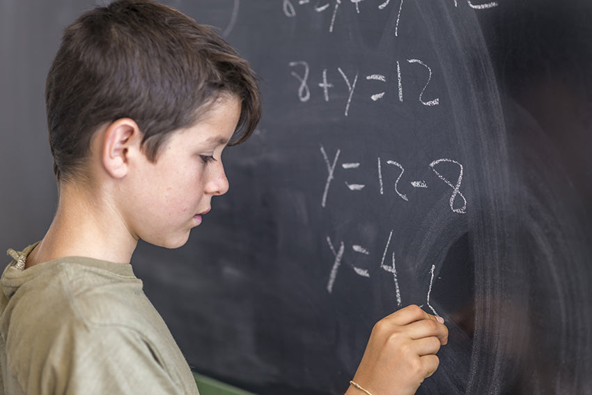 Child with ADHD doing math at chalkboard
