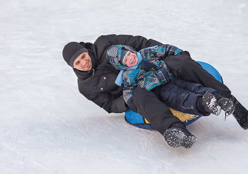 Child with ADHD on sled with dad
