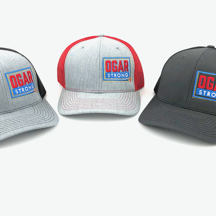Three mesh style trucker hats in black mesh - grey front panel, red mesh - grey front panel and black mesh and black front panel all have the Ogar Strong Logo embroidered on the front left panel
