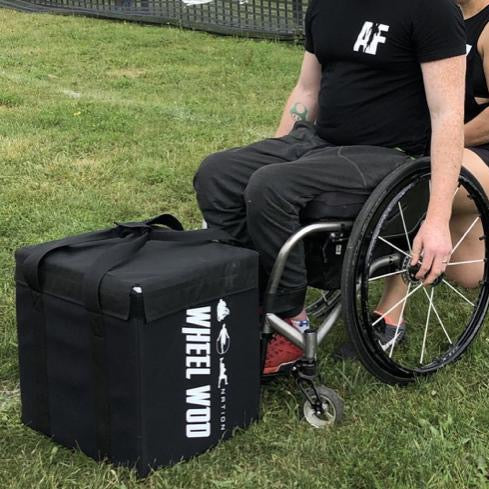 Wheelchair Athlete Josh young in a wheelchair about to pickup a square cushioned box made with black denier material and weighted for workouts called The Package.
