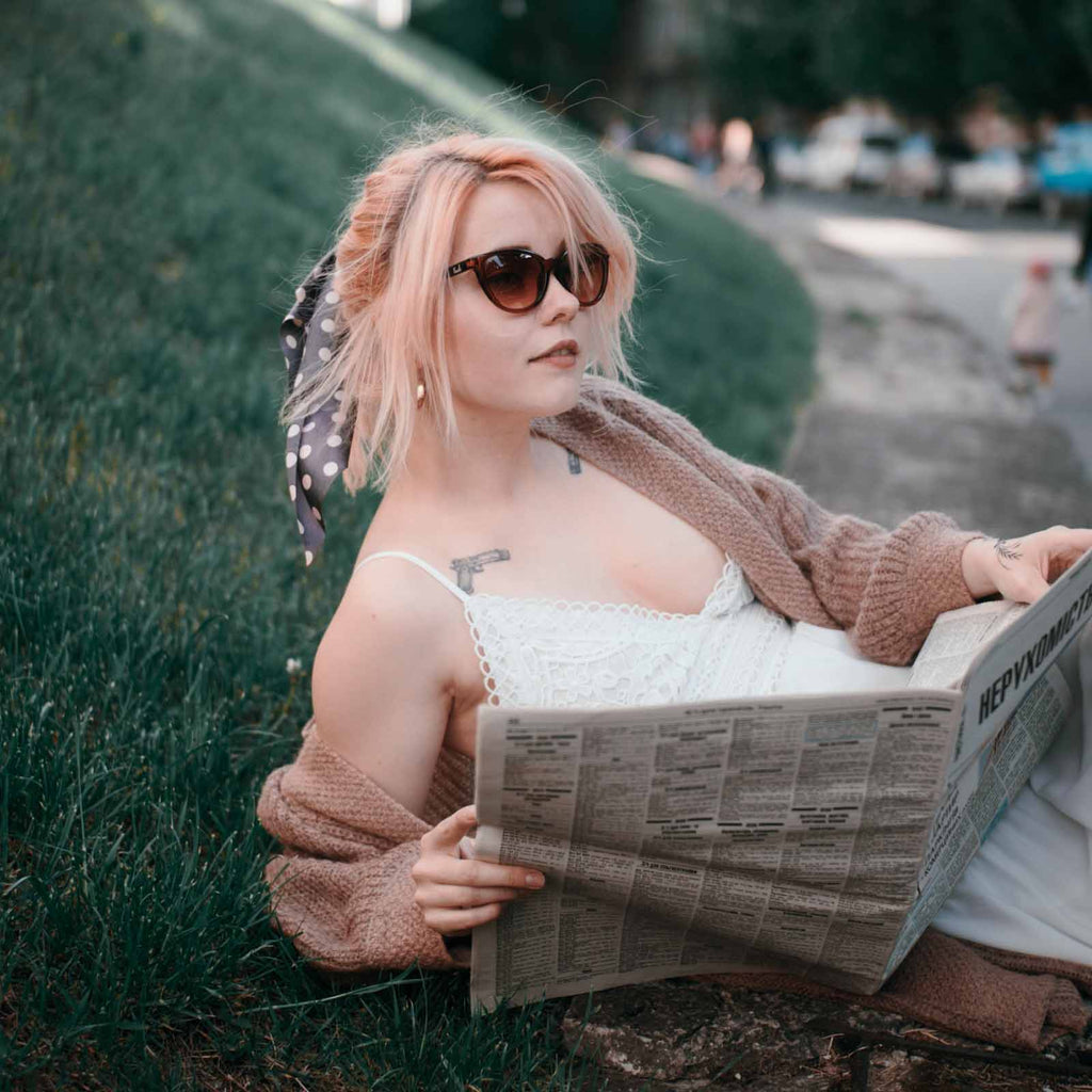 these lightweight sunglasses are ideal for every day use such as here where the model is reading a newspaper on a summers day