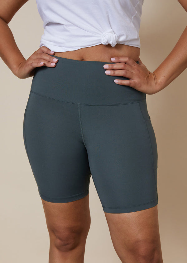 High waisted green bike shorts with side leg phone pockets