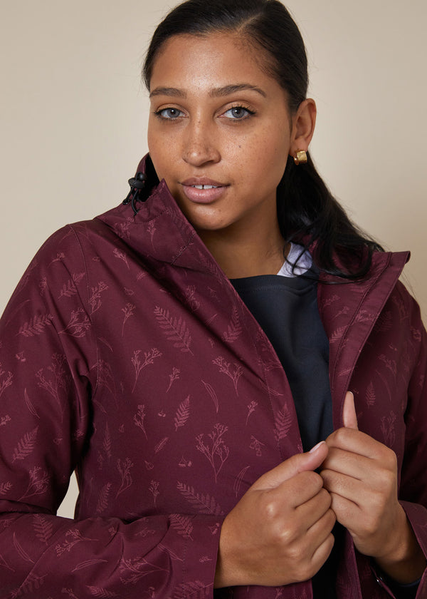 Waterproof plum raincoat with australian botanical fine print in lighter plum, with hood, zip and adjustable toggles