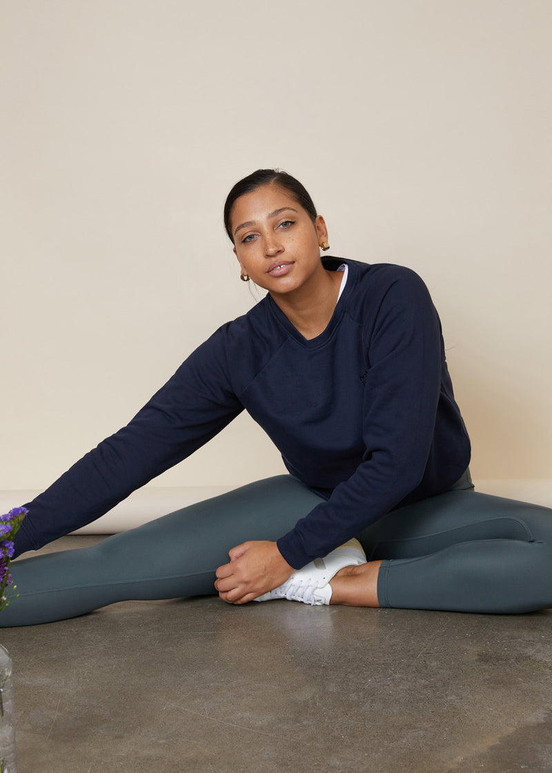 Model stretching sitting down wearing green leggings