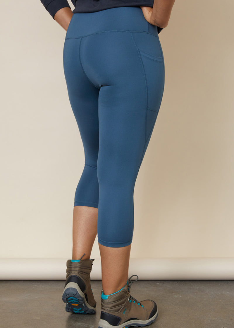 Model in 3/4 light mid blue legging back view, showing side phone pocket