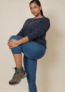 Model stretching wearing 3/4 light mid blue legging with phone pocket