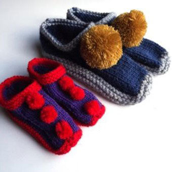These beautiful handknitted slippers have had large matching pompoms sewn onto them.