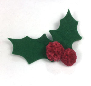 Simple Christmas holly decorations are made by cutting holly leaf shapes from green felt and stitching through them with red pompom 'berries' These could be made into handmade cards or a simple decoration for a present.